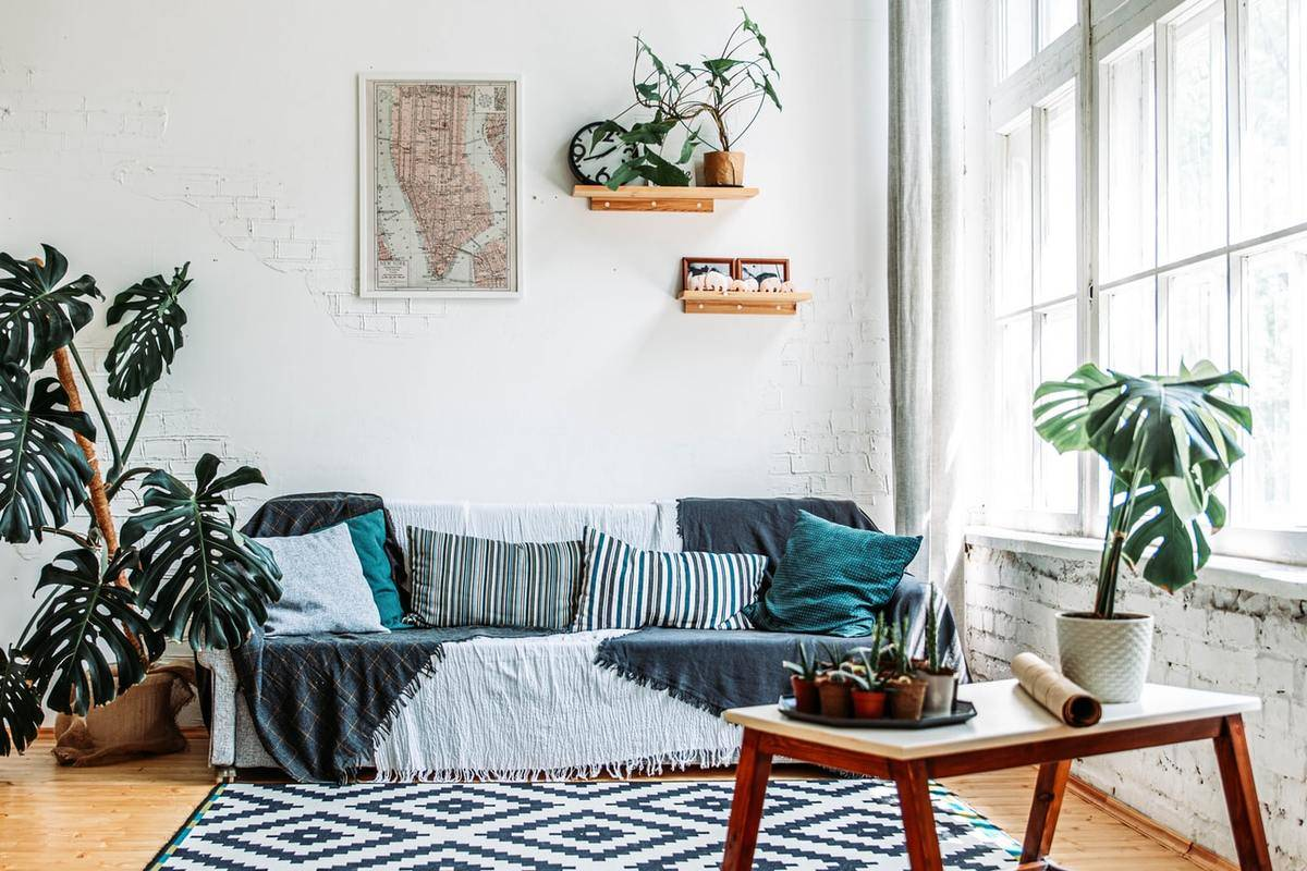 A living room couch is covered with a pattern throw blanket and pillows.