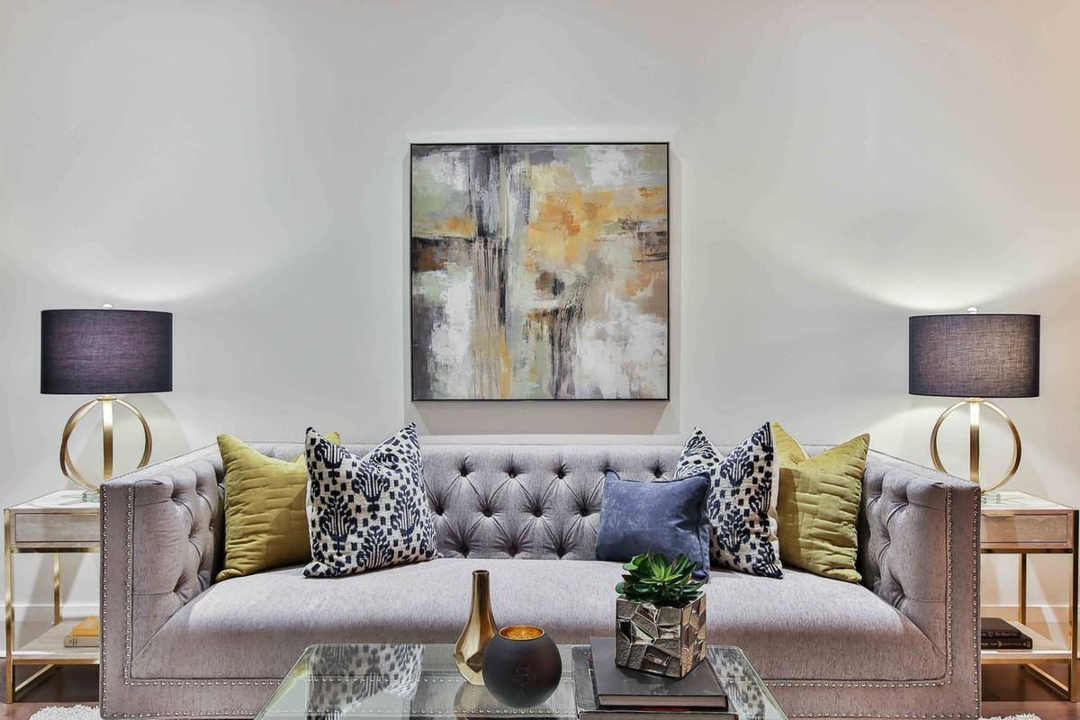 A plush sofa features dramatic pillows and an abstract art piece above it.