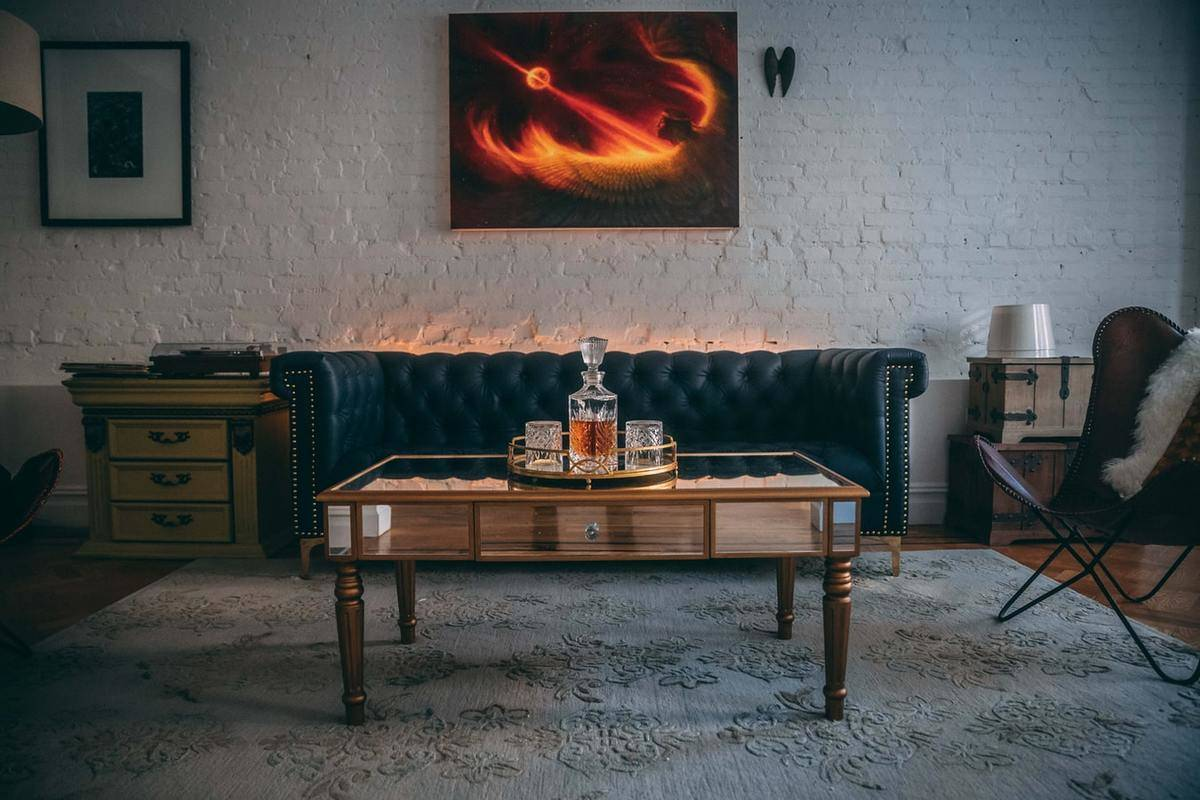 A dark industrial living room has a leather couch and chair with a fiery painting on the wall.
