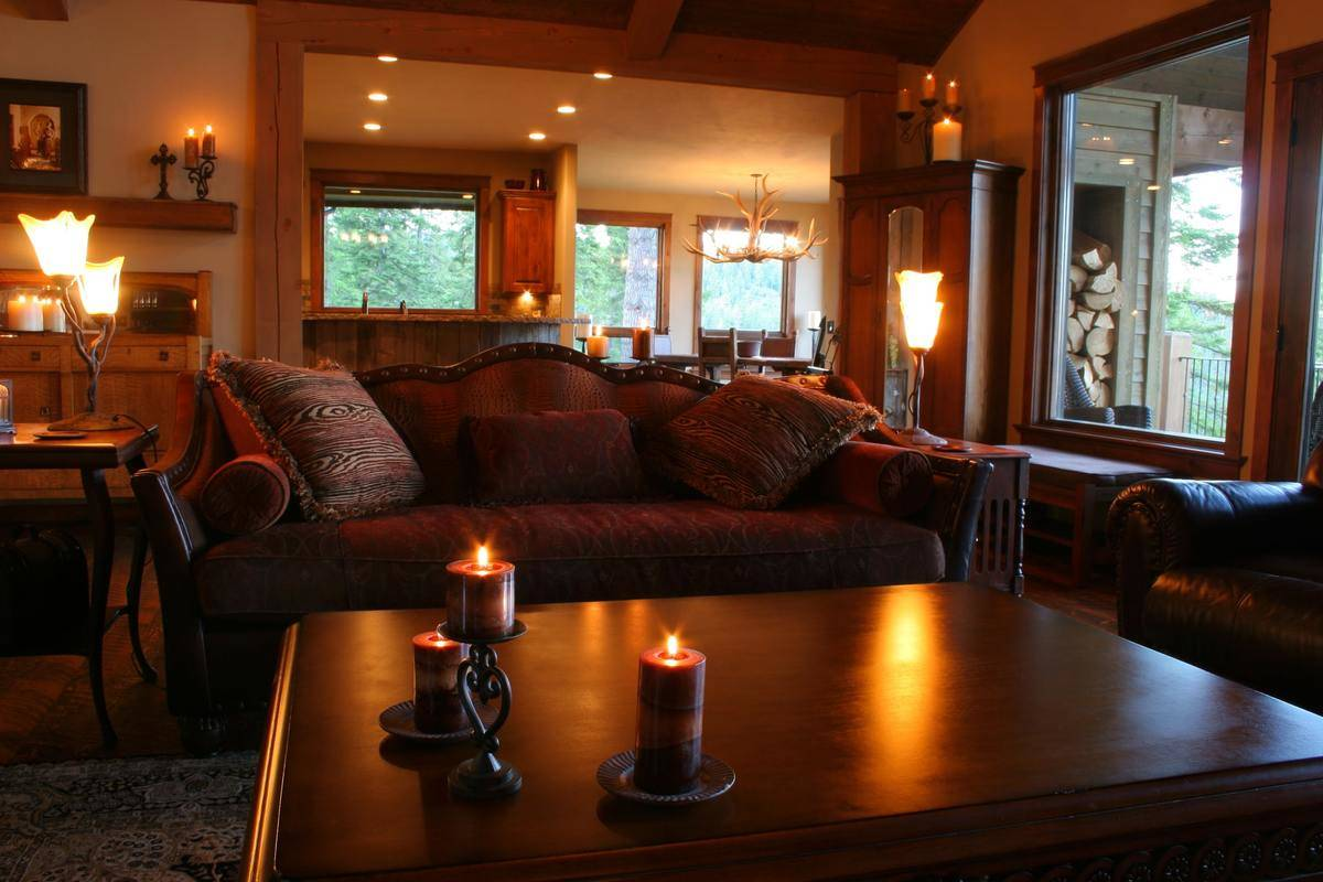 A deep red and brown living room has many lit candles and lamps.