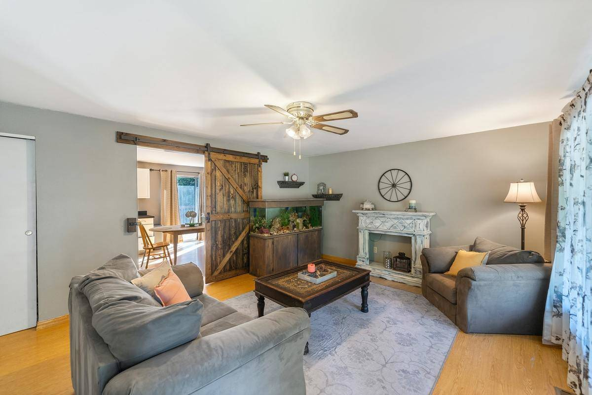 A living room has rustic distressed furniture and a wooden wheel on the wheel.