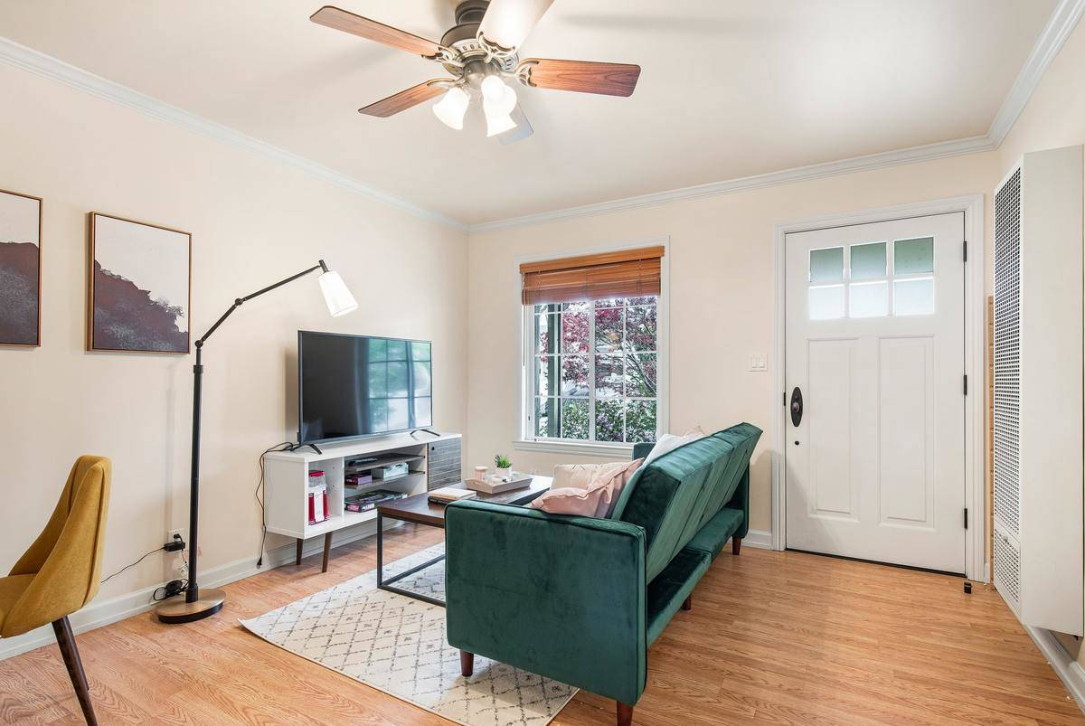 A living room is separated from the entryway by the couch.