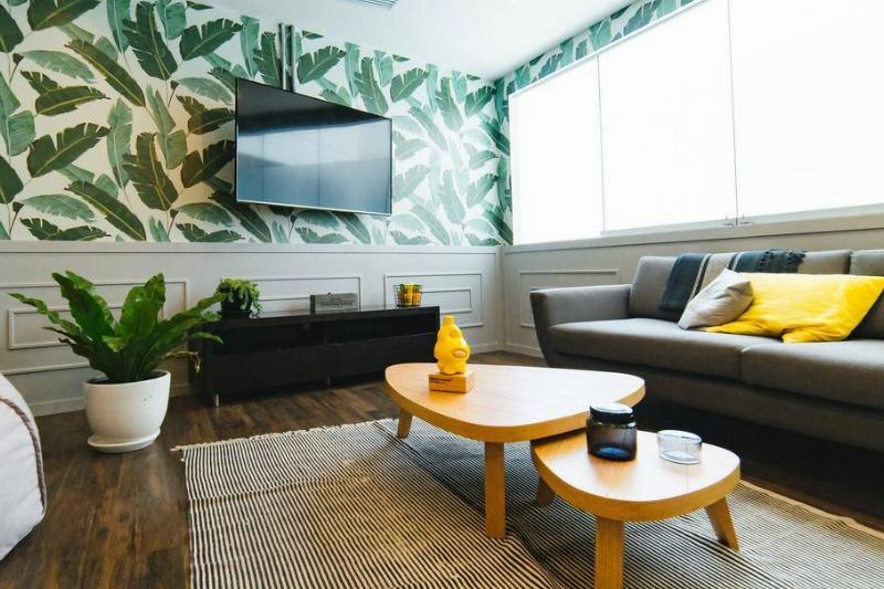 A living room has a dramatic leaf-designed wallpaper.