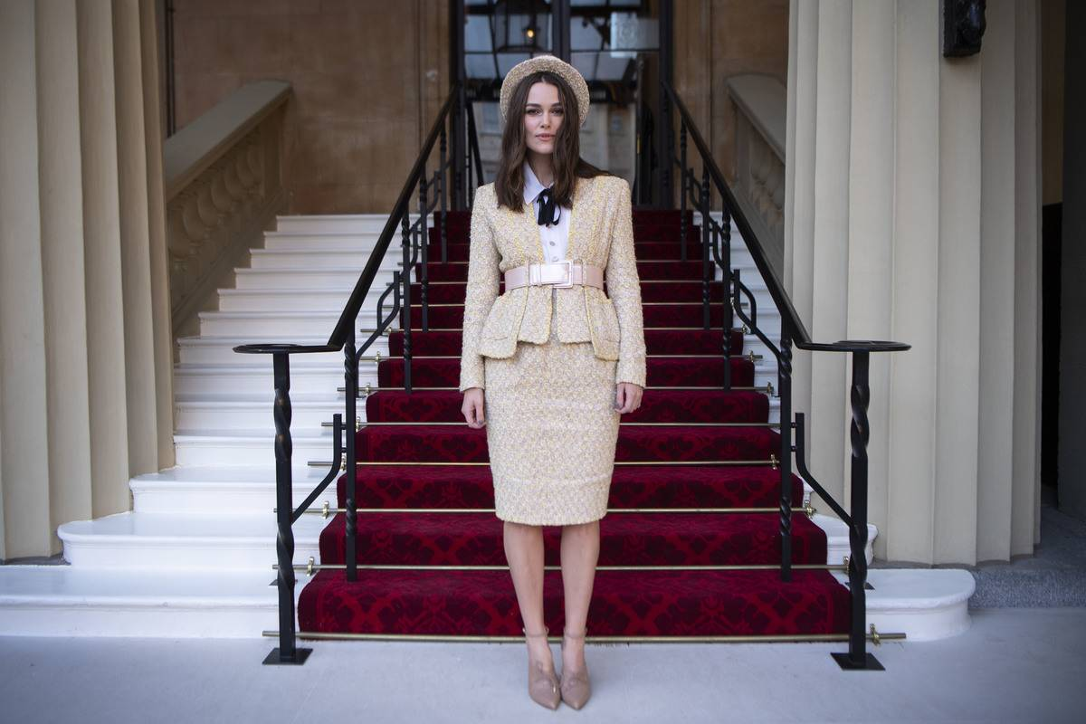 Actress Keira Knightley stands in front of Buckingham Palace.