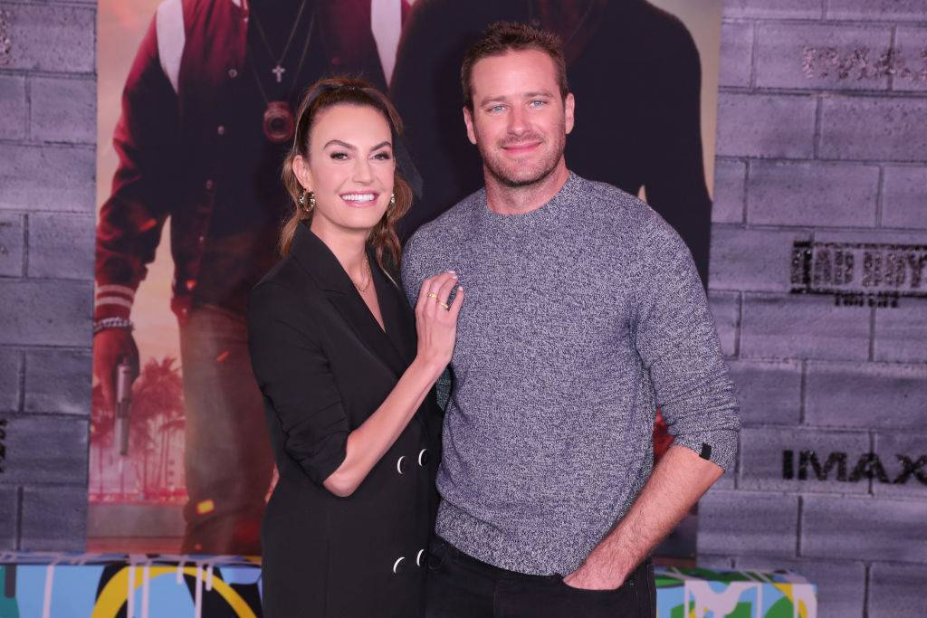 armie hammer and elizabeth chambers posing on the red carpet