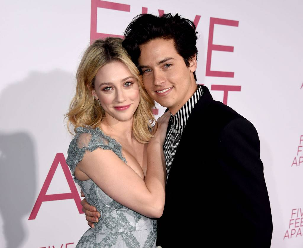 cole sprouse and lili reinhart smiling for a photo on a red carpet