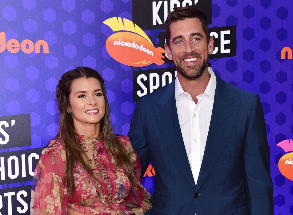 danica patrick and aaron rodgers posing on the red carpet