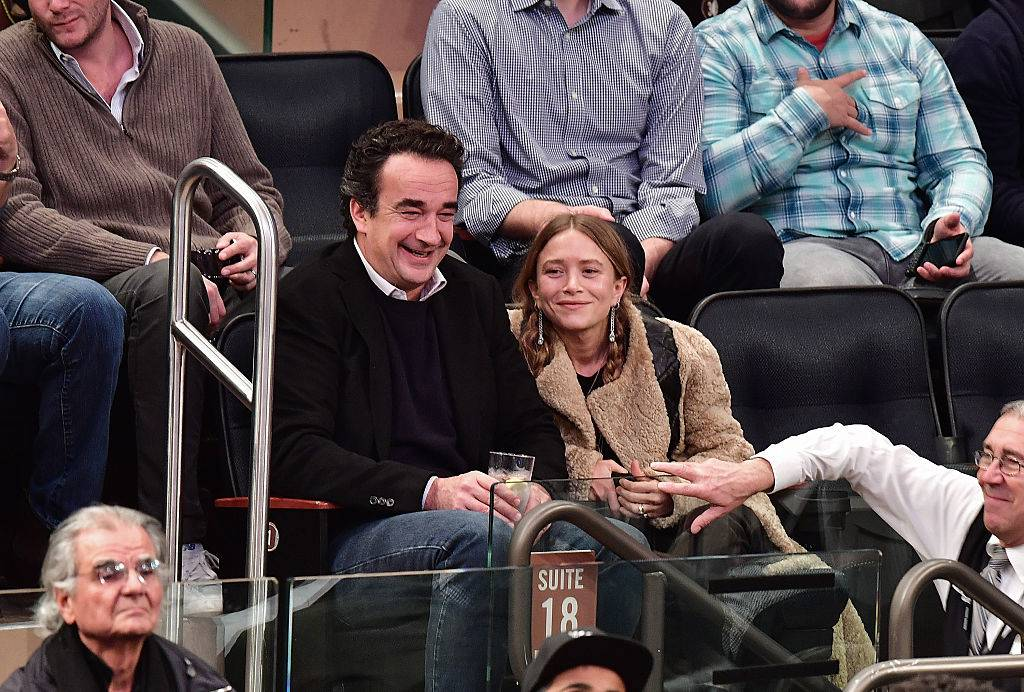 mary-kate olsen and olivier sarkozy watching a sports game