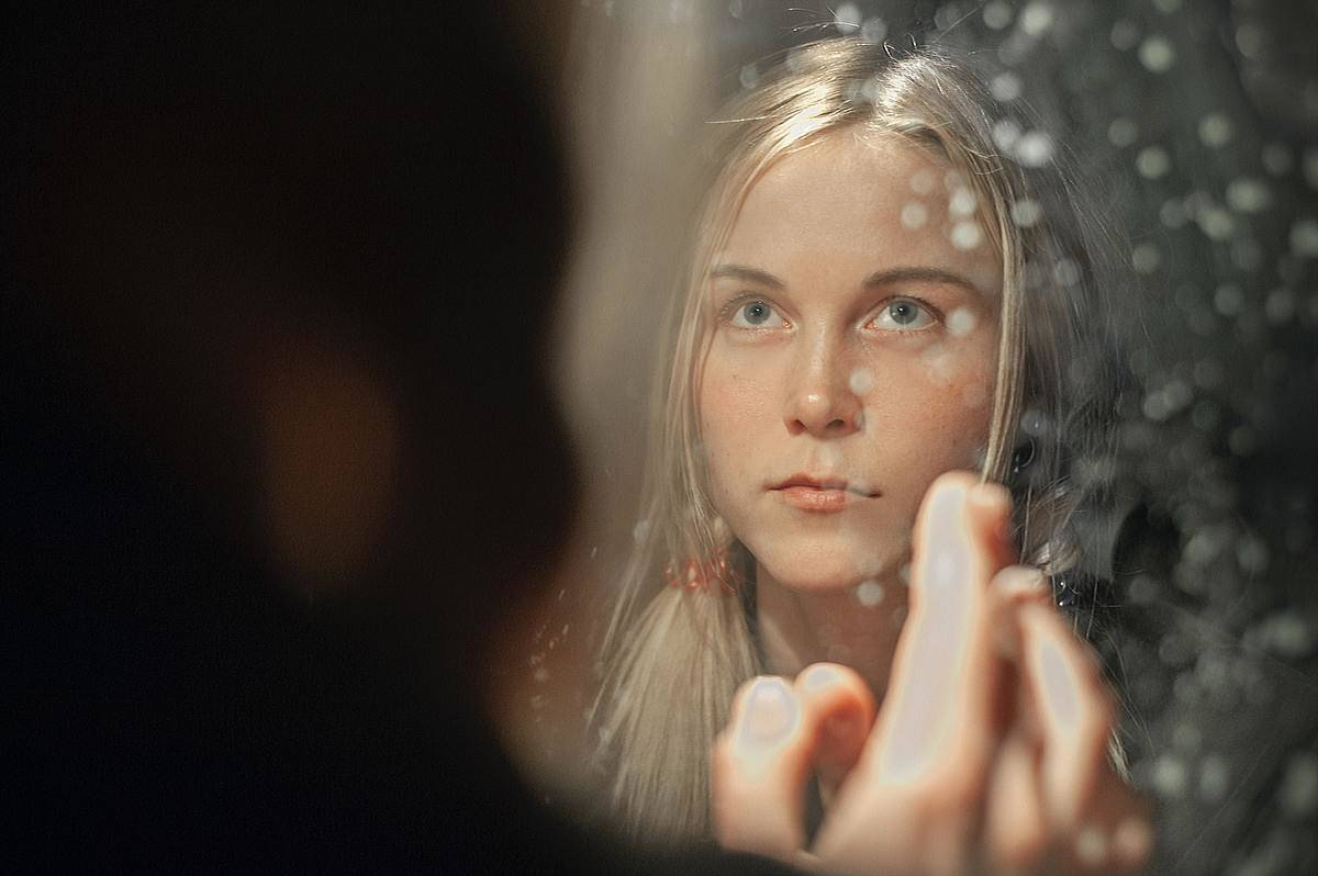 a girl looking in a mirror