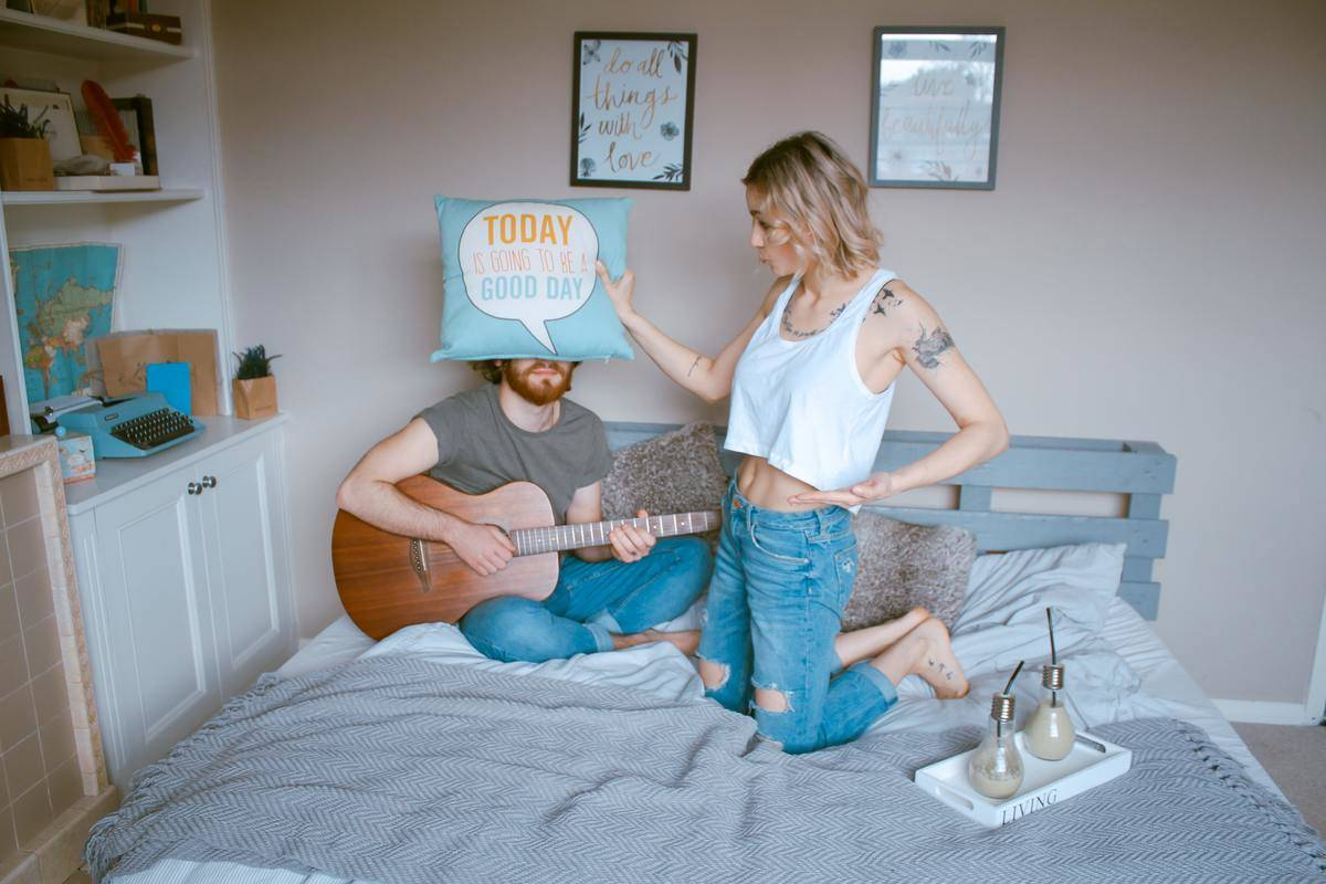 couple posing on a bed with a pillow and guitar
