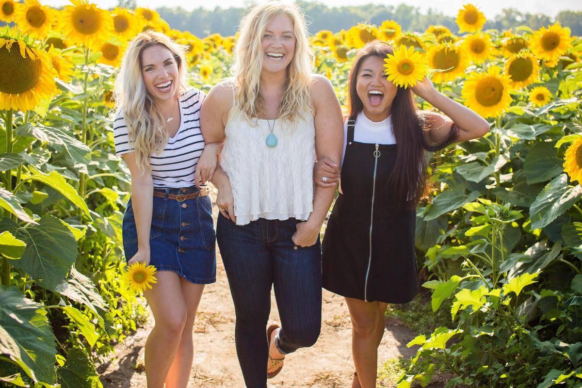 three girls smiling near sunflowers