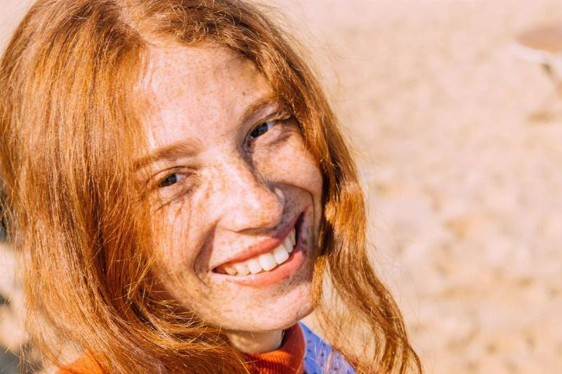 a girl with red hair and freckles smiling