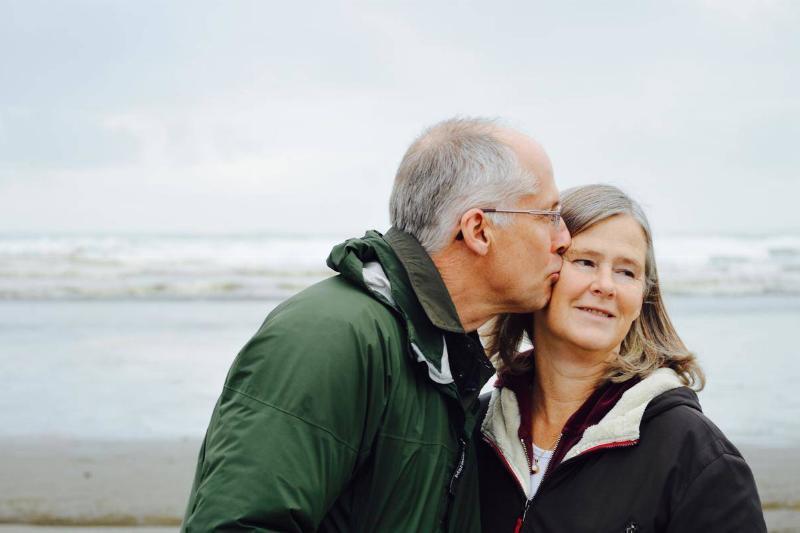 a senior man giving a kiss on the cheek to a senior woman