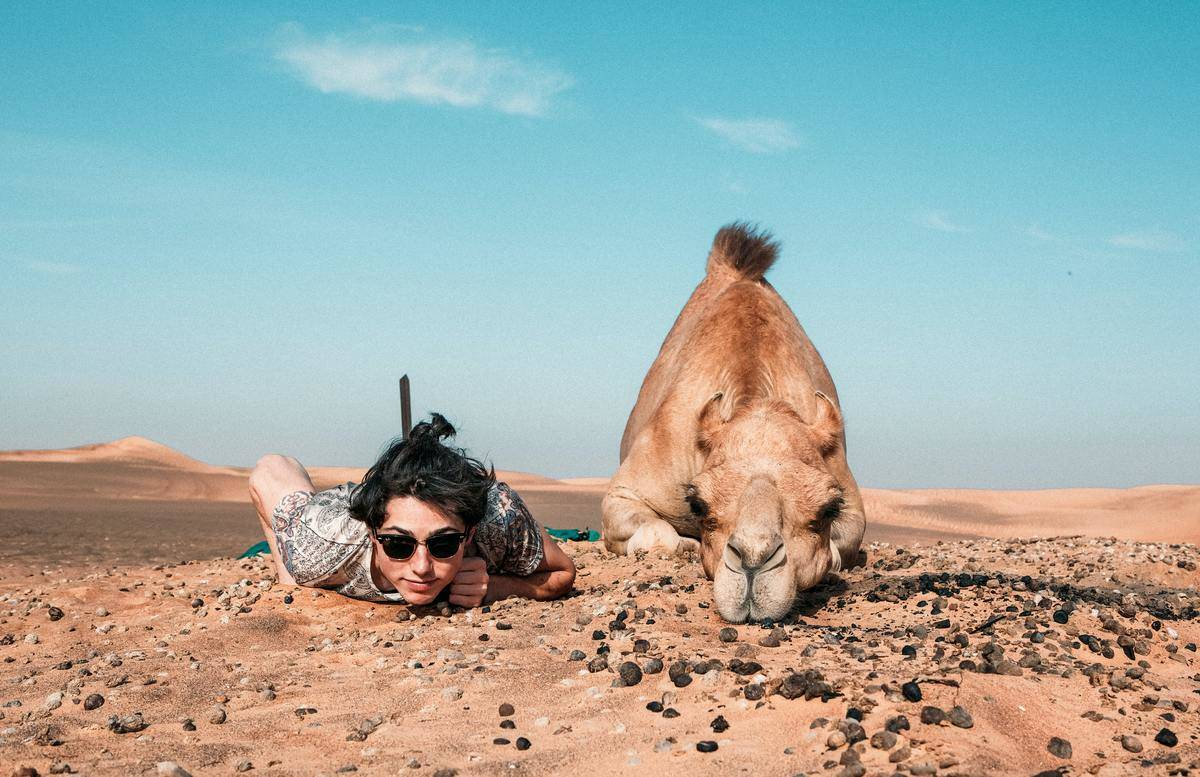 a boy and a camel laying in the desert
