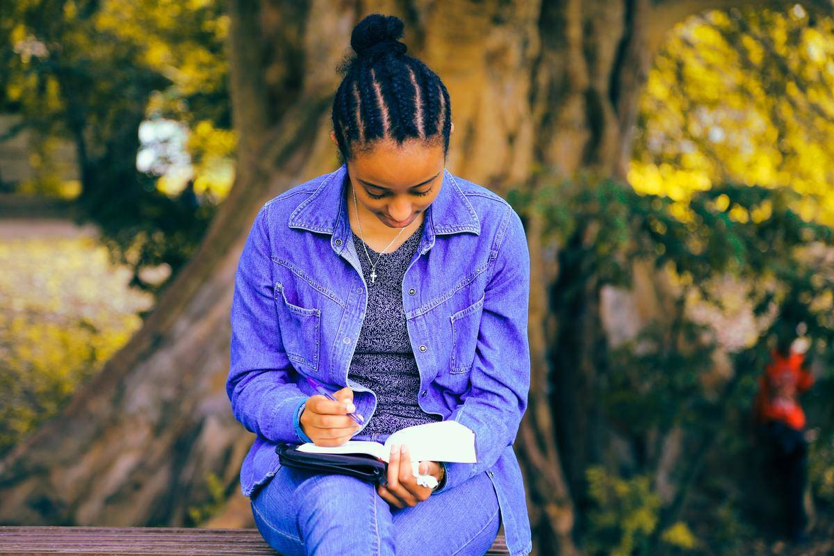 woman writing in a notebook by a tree
